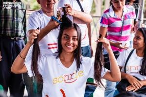 Una joven adventista sostiene su cabello con una sonrisa el pasado 8 de agosto de 2014 mientras se aprestan a cortárselo en Caracas, Venezuela. Unos 350 miembros de iglesia donaron su cabello para ayudar a las mujeres y los niños con cáncer en todo el país, durante el impacto llevado a cabo por la iglesia en toda la ciudad hace unos días. [Fotografías por cortesía de la Unión Venezolana Oriental/DIA]