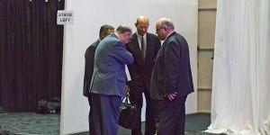 Ted N. C. Wilson habla con Robert Lemon, el tesorero saliente, el tesorero entrante Juan Prestol-Puesán, y Karnik Doukmetzian, asesor legal general de la Asociación General detrás de la plataforma, antes de hablar a los delegados sobre el voto electrónico. Imagen de la AR