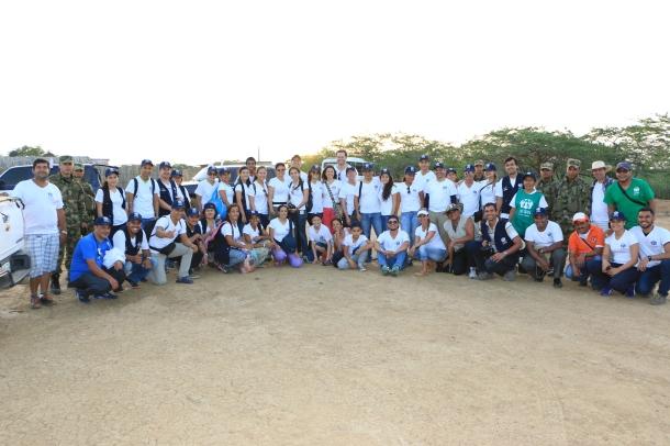 75 voluntarios provenientes de diferentes ciudades del país y del exterior posan para una foto en la puesta del sol del primer día de actividades solidarias organizadas por ADRA Colombia en La Guajira
